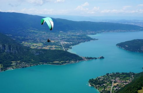 Paraglider soaring high above the lake